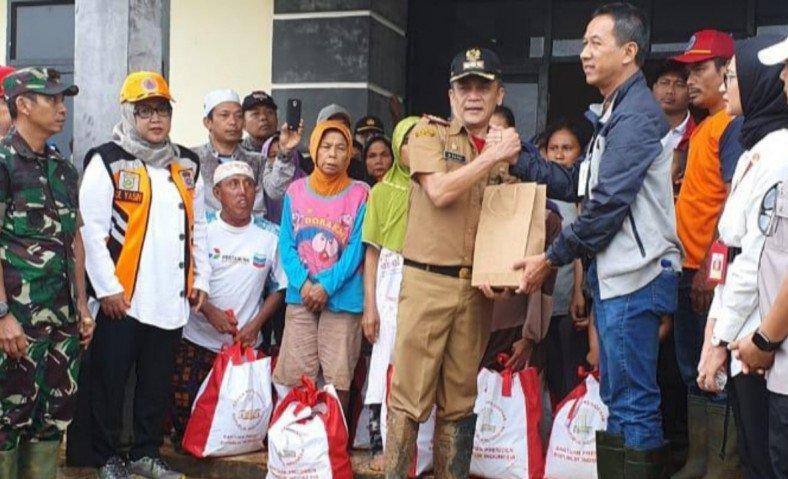 Kepala Sekretariat Kepresidenan, Heru Budi Hartono (kanan) menyerahkan bantuan dari Presiden Jokowi di Kecamatan Sukajaya, Kabupaten Bogor, Minggu (5/1/2020). ANTARA/Humas Pemkab Bogor