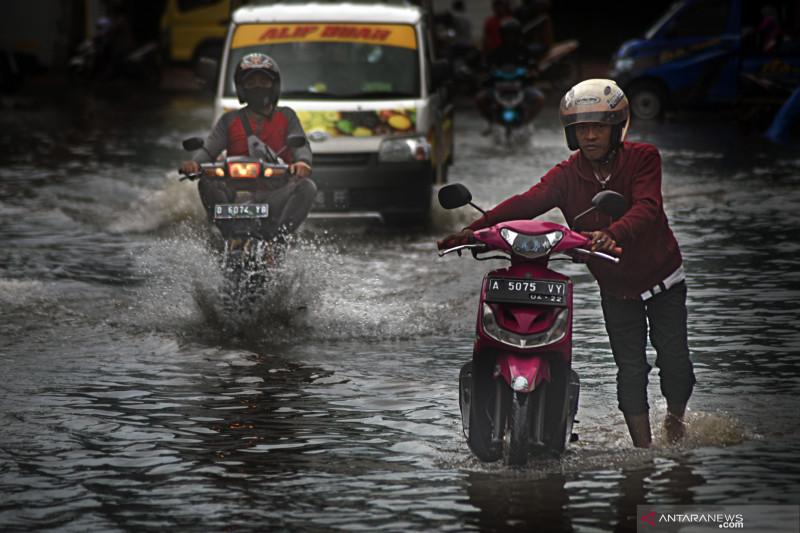 Ilustrasi--Warga mendorong sepeda motor melintasi genangan banjir di kawasan Pasar Induk Rau, Serang, Banten. (Foto: ANTARA/Fathul Rahman)
